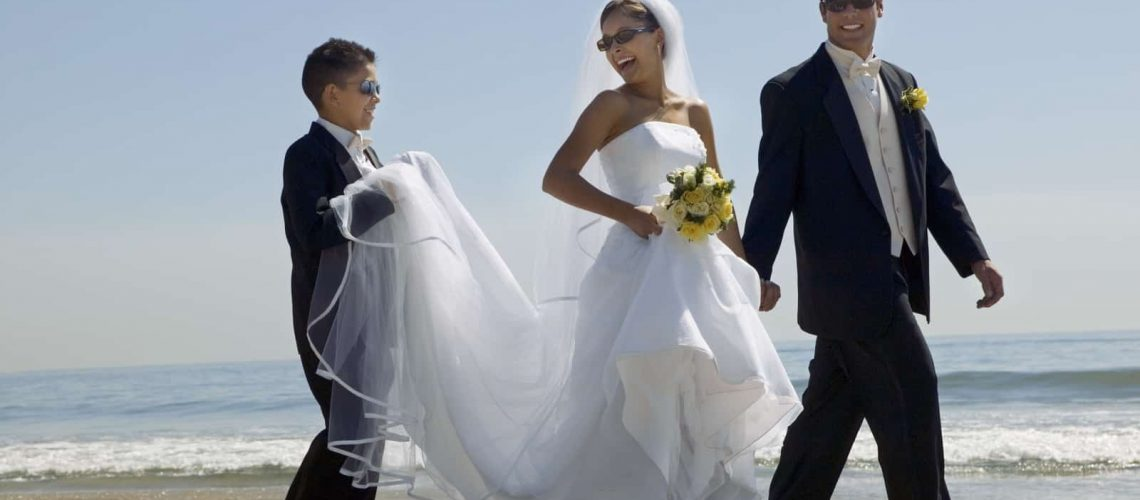 bride-and-groom-with-brother-walking-on-beach