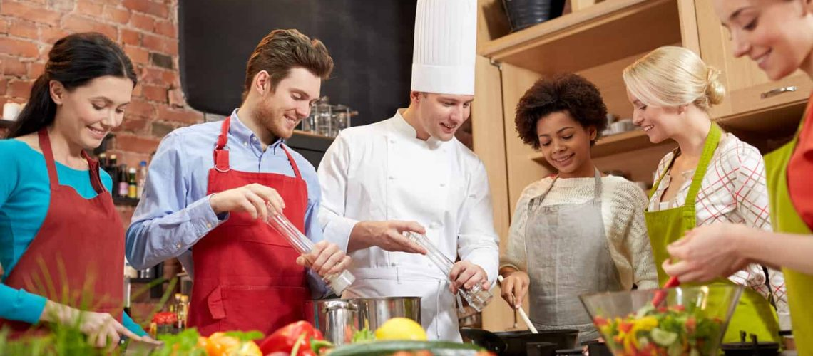 happy-friends-and-chef-cook-cooking-in-kitchen